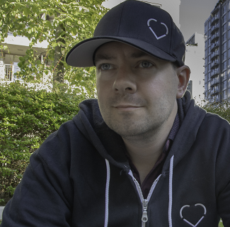 Chris is wearing a black hoodie and a black baseball cap that both have a white heart outline logo. He is staring into the distance and smiling.