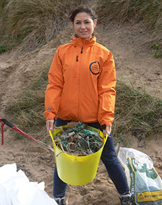 Joanna Toole stands in an orange waterproof coat and jeans collecting beach debris in a yellow plastic bucket