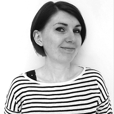 Shown in black and white, Meg stands in front of a white background and smiles at the camera. She is wearing a white and black stripy top