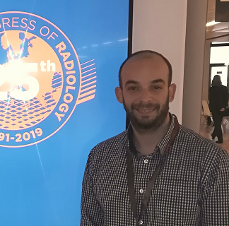 Nikolaos stands to the right of a blue screen that has the Congress for Radiology logo. He poses for the camera in a shirt and is smiling.