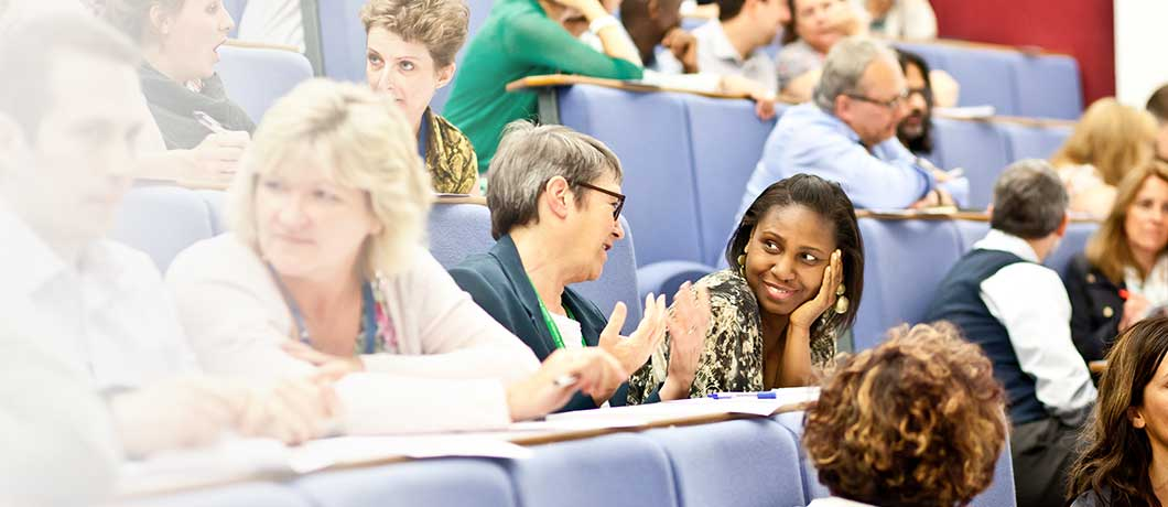 Two people talking at a conference in a lecture theatre