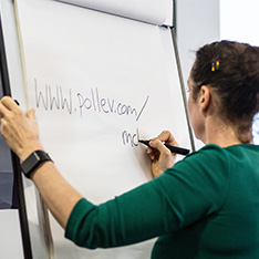Woman writing a Poll Everywhere URL on a flip chart