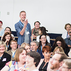 Man speaking and pointing in lecture theatre at conference 2013