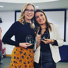 University students Alessia and Emma holding awards