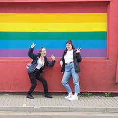 Sociology student Amy and friend in front of a painted rainbow flag