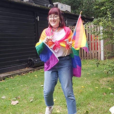 Sociology student Amy draped in a large rainbow flag