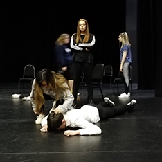 Group of drama students rehearsing a scene from a play