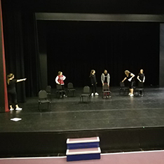 Group of drama students rehearsing on a theatre stage