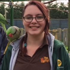 Zoology student Jessica with a parrot on her shoulder