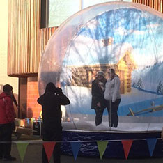 People being photographed in front of a giant snow globe