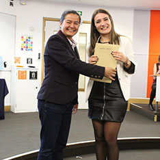 Student Ambassador Alessia receiving the Intern of the Year Award from a member of staff