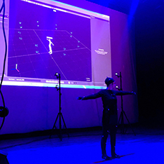 Sabrina Minter working on motion capture in front of a big screen
