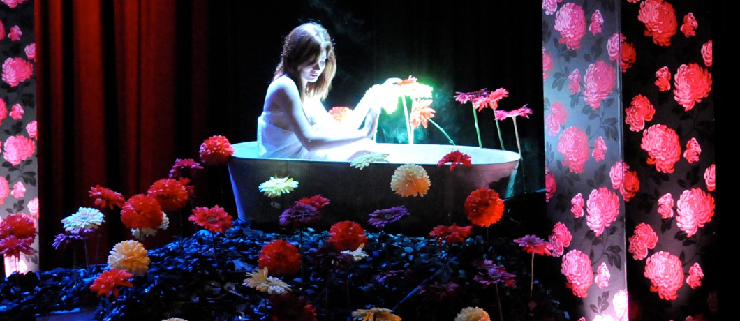Theatre set of a woman in a bathtub on a mound of flowers