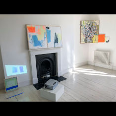 Pieces of fine art work in a white room with a black fireplace