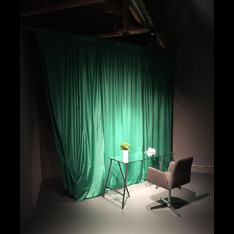 A table and chair in front of a green curtain