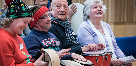 A group of older people playing percussion instruments