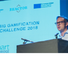 A speaker at a podium with a presentation behind him at REACTOR Big Gamification Challenge Seminar