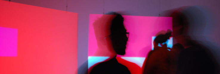 Blurred image of two people in a red and pink room