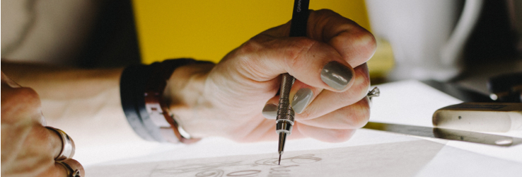 A hand holding a pen and drawing an image on a transparency