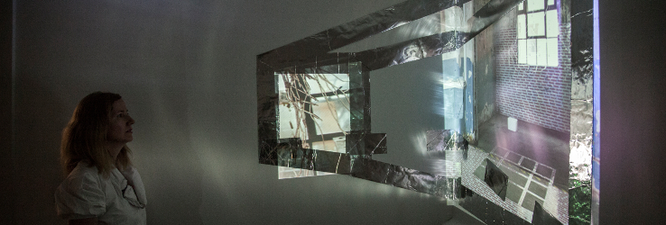A woman looking at a multiscreen installation created from video and silver tape