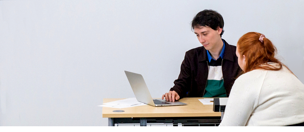A man on a reception desk looking at a laptop with a female client