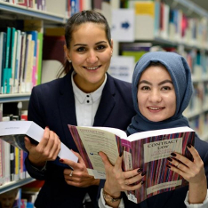 Two female law students reading law books in the library