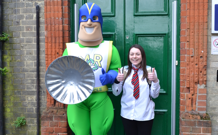 Drama student Laura Mackie in schoolgirl costume next to Michael the Recycling Superhero, with bin-lid shield