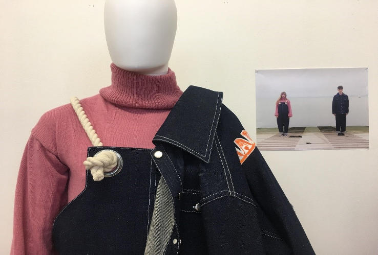 A mannequin wearing a pink jumper and denim dungarees, with a denim jacket over its shoulder