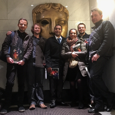 The filmmakers of 'The Crossing' in front of a large BAFTA mask at the AHRC awards ceremony