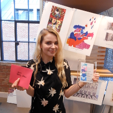 BA (Hons) Illustration student Ursula Tolliday-Bolland holding her runner-up award for the Batsford Prize 2017 in front of a display of her illustration work