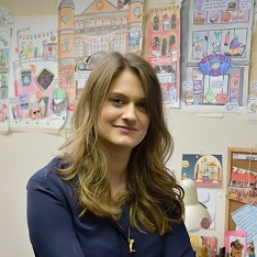 Elys Dolan in front of a display of her illustrations