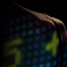 Screenshot of a woman's shoulder with digital numbers and a square matrix projected on it