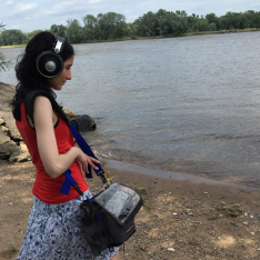 Dr Mariana Lopez recording audio on the shore of a lake