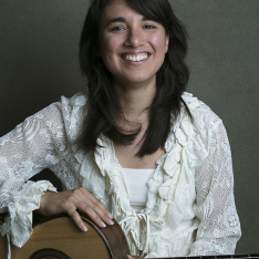 Woman sat holding a guitar, smiling at the camera