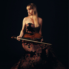 a woman sat posed with a violin against a black background