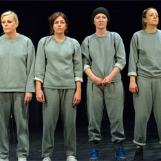 four women, stood in a line, dressed in identical grey prison garb