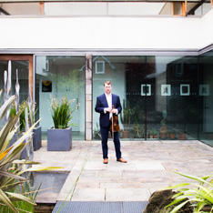 Peter Bussereau, stood in a patio garden, holding a violin