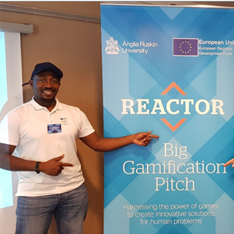 Dennis Aguma standing in front of a Reactor branded banner