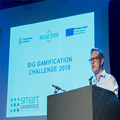 Man stood at a podium, at REACTOR Showcase, with Big Gamification Challenge 2018 presentation slides projected behind him