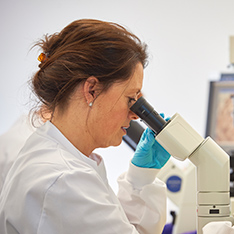 Female healthcare professional looking through microscope