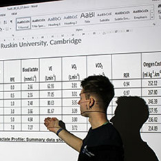 Person giving a presentation, gesturing towards data on a screen
