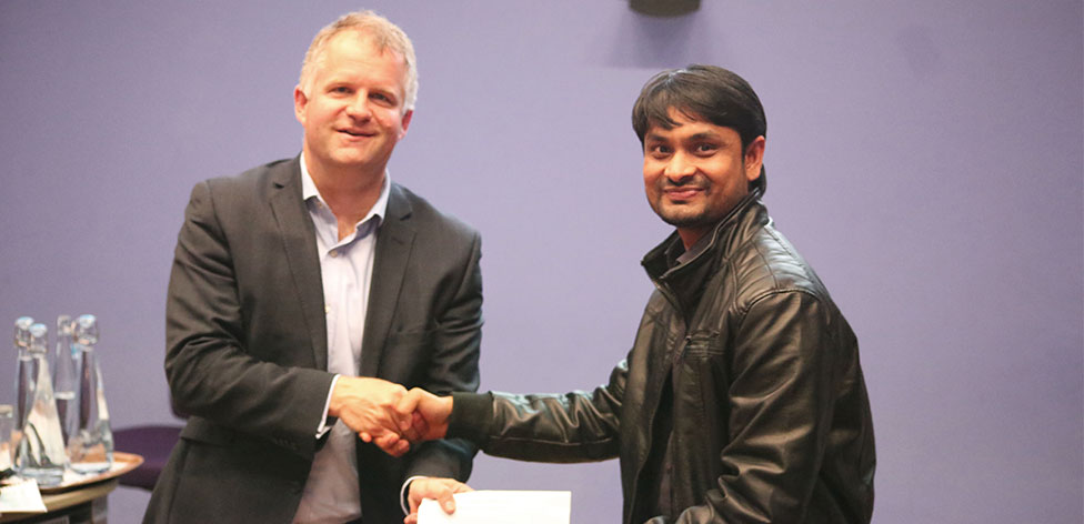 VC Prof Iain Martin presenting a prize to PhD student Md Mahmudul Hasan for his poster submission titled 'Let me be: a gamified app to choose STEM careers'.