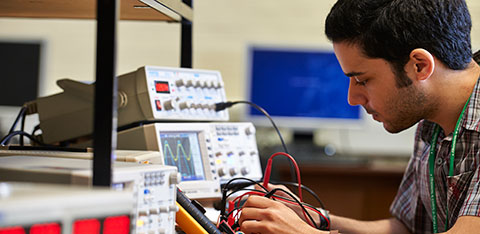 Research student working in an electronics lab