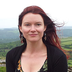 Head shot of Anglia Ruskin lecturer, Dannielle Green, stood outside with fields in the background