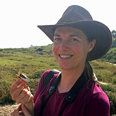 Dr Sophie Mowles out in the field holding a crab