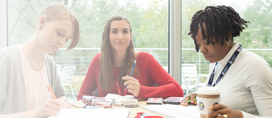 Three Anglia Ruskin Business School students sat round a table studying