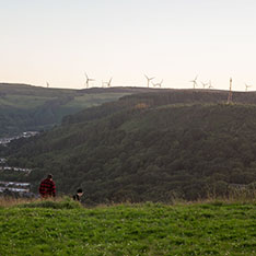 Two people walking on a hillside with wind turbines seen in the distance