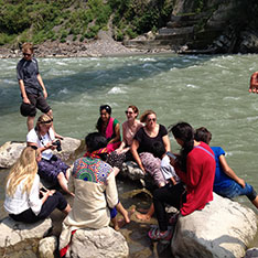 Volunteers in Sainji sitting next to the river