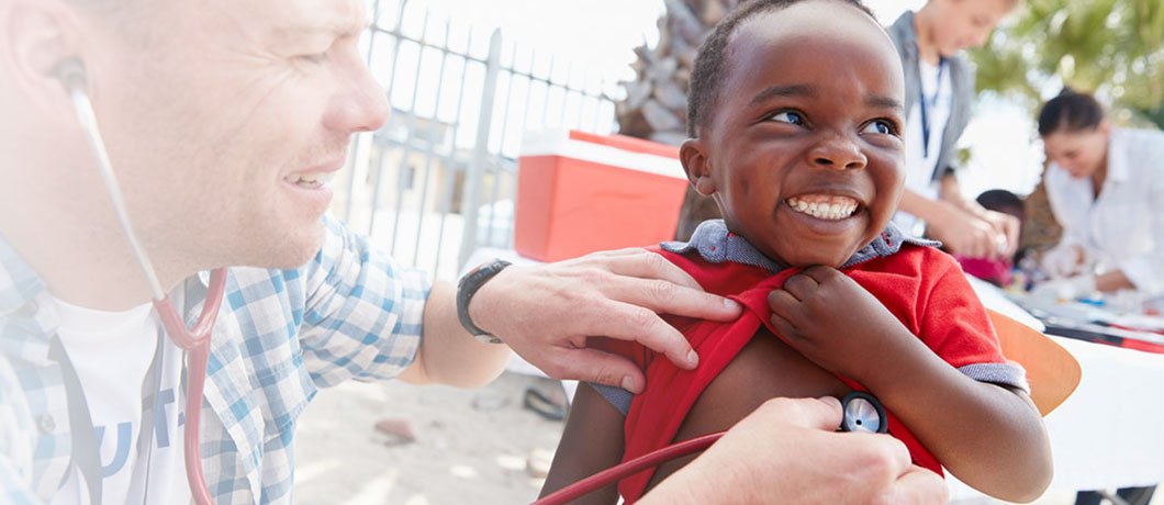Man listening to child's heart with stethoscope