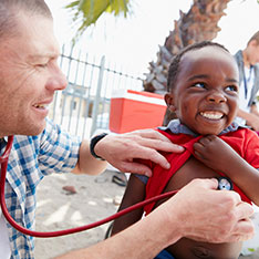Doctor listening to heart of smiling child as part of global healthcare effort